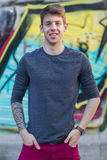 Handsome male teenager tattooed arm in grey shirt. Young handsome male teenager with tattooed arm in grey long sleeve shirt smiling looking at camera outdoors stock image