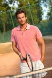 Handsome male tennis player smiling. Handsome young male tennis player smiling on tennis court Stock Photos