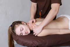 Handsome male therapist conducts manual massage procedure for fe. Strong young men masseur conducts restoring procedure and drives hands along spine and along Royalty Free Stock Image