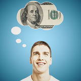 Handsome male thinking about money. Handsome young man thinking about money on bright blue background royalty free stock image