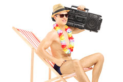 Handsome male tourist relaxing on a chair with boombox on his sh. Oulder, isolated on white background stock image