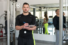 Handsome Male Trainer With Clipboard In A Gym. Personal Trainer With Clipboard Monitors People While They Exercise In A Gym Or Fitness Club Stock Photography