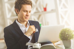 Handsome male using laptop. Portrait of handsome young male using laptop at workplace Royalty Free Stock Image