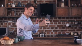 Handsome male using mobile phone in kitchen stock video