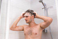 Handsome male washing his hair with both hands Royalty Free Stock Photo