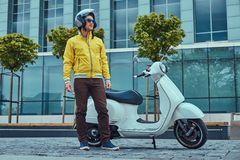 Handsome male wearing brown pants and yellow jacket, in sunglasses and helmet, standing near classic Italian scooter. A handsome male wearing brown pants and Royalty Free Stock Photography