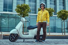 Handsome male wearing brown pants and yellow jacket, in sunglasses and helmet, standing near classic Italian scooter. A handsome male wearing brown pants and Royalty Free Stock Images
