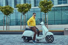 Handsome male wearing brown pants yellow jacket and sunglasses, sitting on a white classic Italian scooter against a. A handsome male wearing brown pants yellow Royalty Free Stock Images