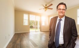 Handsome Male Wearing Suit and Tie In Empty Room of House. Handsome Male Wearing Suit and Tie In Empty Room of a New House stock photography