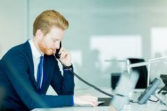 A handsome male worker in a call center office talking on a phon Stock Photo