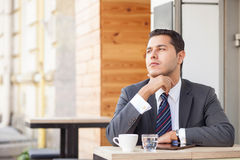 Handsome male worker is resting in cafe. Cheerful young businessman is sitting and thinking seriously in cafeteria outdoors. He is touching his chin and looking Stock Photography
