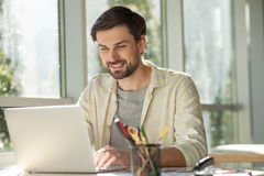Handsome male worker us using a notebook Royalty Free Stock Images