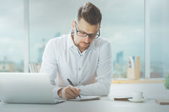 Handsome male working on project. Handsome young male working on project at modern office desk Stock Photo