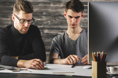 Handsome males doing paperwork. Portrait of handsome european males doing paperwork at desk with devices, supplies and other items. Teamwork and project concept Royalty Free Stock Images