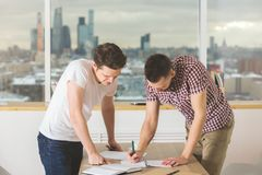Handsome males doing paperwork side. Side view of handsome males doing paperwork ar modern office desk. Business, project, teamwork and communication concept Royalty Free Stock Photos
