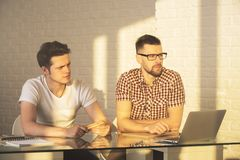 Handsome males working on project. Two handsome males working on project in modern office. Success, teamwork, discussion and meeting concept Royalty Free Stock Photography