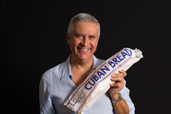 Handsome man. Handsome middle age man  holding a loaf of Cuban bread on a black background Stock Photography