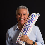 Handsome man. Handsome middle age man  holding a loaf of Cuban bread on a black background Stock Images