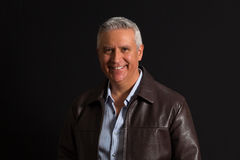 Handsome man. Handsome middle age man wearing a leather coat on a black background Stock Image