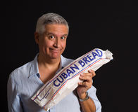 Handsome man. Handsome middle age man  holding a loaf of Cuban bread on a black background Royalty Free Stock Photo