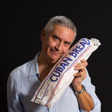 Handsome man. Handsome middle age man  holding a loaf of Cuban bread on a black background Royalty Free Stock Image