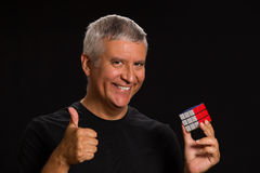 Handsome man. Handsome middle age man in a studio portrait holding a game cube Stock Photo