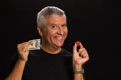 Handsome man. Handsome middle age man in a studio portrait holding a Las Vegas craps game dice and hundred dollar bill royalty free stock photos