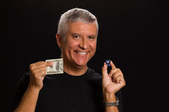 Handsome man. Handsome middle age man in a studio portrait holding a Las Vegas craps game dice and hundred dollar bill stock photos