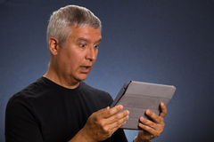 Handsome man. Handsome middle age man holding a tablet computer in a studio portrait Royalty Free Stock Photo