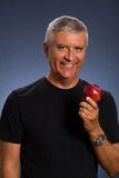 Handsome man. Handsome middle age man with an apple in a studio portrait Royalty Free Stock Photography