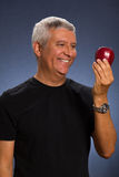 Handsome man. Handsome middle age man with an apple in a studio portrait Royalty Free Stock Photo