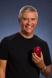 Handsome man. Handsome middle age man with an apple in a studio portrait Stock Photo