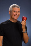 Handsome man. Handsome middle age man with an apple in a studio portrait Stock Images