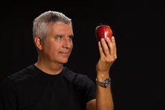 Handsome man. Handsome middle age man with an apple in a studio portrait Royalty Free Stock Image