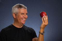 Handsome man. Handsome middle age man with an apple in a studio portrait Stock Photography