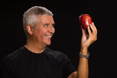 Handsome man. Handsome middle age man with an apple in a studio portrait Stock Photos