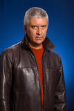 Handsome man. Handsome middle age man in a studio portrait wearing a leather jacket Stock Image