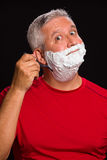 Handsome man. Handsome middle age man with shave cream on a black background Stock Image