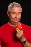Handsome man. Handsome middle age man holding a tomato on a black background Royalty Free Stock Photography