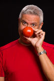 Handsome man. Handsome middle age man holding a tomato over his nose on a black background Royalty Free Stock Photography