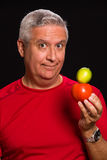 Handsome man. Handsome middle age man holding a tomato and lime on a black background Stock Photo