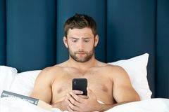 Shirtless hunky man with beard lies naked in bed using mobile phone stock image