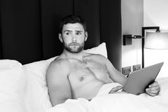 Shirtless hunky man with beard uses ipad tablet in bed. Handsome man with abs, muscular, hunky body and beard lies naked in between white sheets on bed while stock photography