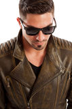 Handsome man acting like a bad boy. Handsome man wearing leather jacket and sunglasses acting like a bad boy stock photo