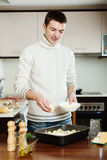 Handsome man adding grated cheese in roasting pan Royalty Free Stock Photos