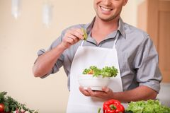 Handsome man adding lime to fresh salad. Royalty Free Stock Photography