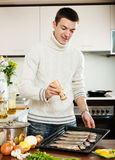 Handsome man adding spices in raw fish Stock Image