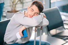 Handsome man in the airport. Exhausted traveler. Tired handsome man in casual clothing sleeping on his luggage while sitting on the rows of chairs in the airport Royalty Free Stock Photography