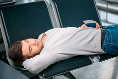 Handsome man in the airport. Time to nap. Tired handsome man in casual clothing sleeping on the rows of chairs in the airport lobby with a ticket and passport in Royalty Free Stock Photography