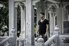 Handsome man in ancient temple. Young man standing on porch of stone temple in Bangkok enjoying surroundings while traveling Royalty Free Stock Images